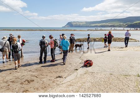 ROBIN HOODS BAY ENGLAND - AUGUST 12: Group of American tourists on vacation visiting the beach. In Robin Hoods Bay North Yorkshire England. On 12th August 2016.