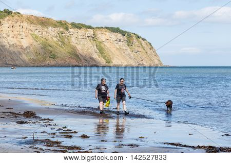 ROBIN HOODS BAY, ENGLAND - AUGUST 12: Two adult women walking with a dog along edge of the sea. In Robin Hoods Bay, North Yorkshire, England. On 12th August 2016.