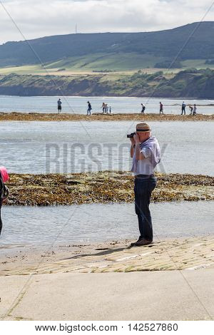 ROBIN HOODS BAY ENGLAND - AUGUST 12: Man taking a photo with a camera. In Robin Hoods Bay North Yorkshire England. On 12th August 2016.