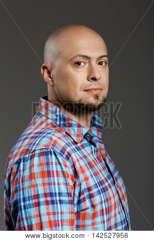 Portrait of confident handsome middle-aged man in plaid shirt smiling at camera over grey background. Copy space.
