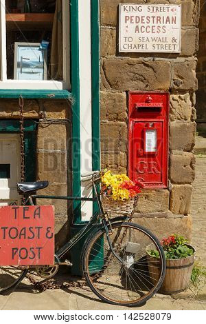 ROBIN HOODS BAY ENGLAND - AUGUST 12: Red Royal Mail postbox set into wall of the old post office on King Street. In Robin Hoods Bay North Yorkshire England. On 12th August 2016.