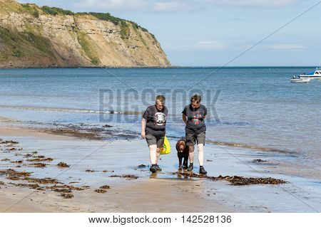 aROBIN HOODS BAY ENGLAND - AUGUST 12: Two adult women walking with a dog along edge of the sea. In Robin Hoods Bay North Yorkshire England. On 12th August 2016.