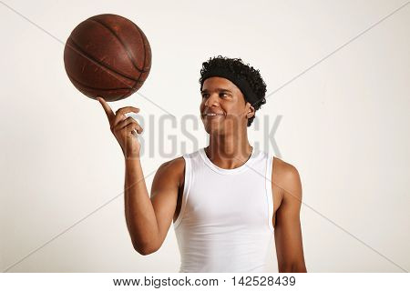 Young Black Athlete Balancing Leather Basketball On Finger