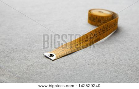 Yellow Measuring Tape On Gray Fabric