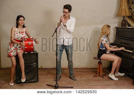 singing trio , girls , boy , drum , microphone , piano , ensemble