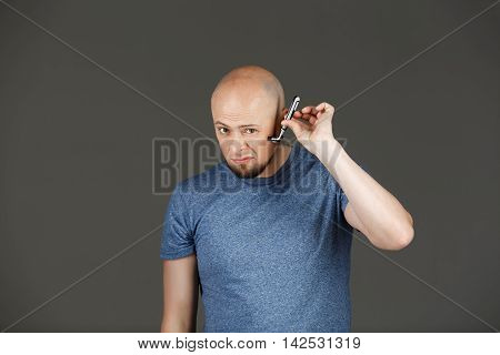 Portrait of funny handsome middle-aged man in grey shirt shaving over dark background. Copy space.