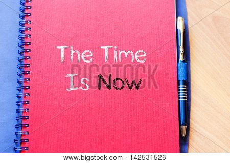 The time is now text concept write on notebook
