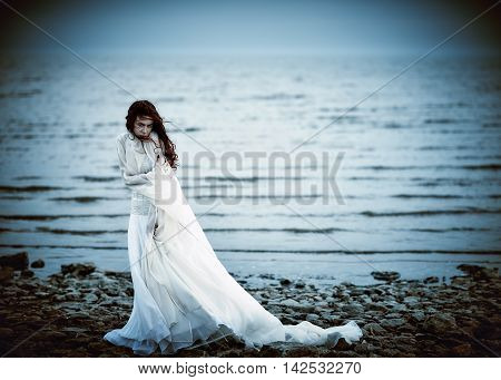 Beautiful sad girl in white dress standing on the sea coast