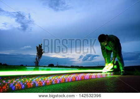 Young Boy Holding Lighting Skateboard Before Speed Movement Captured As Light