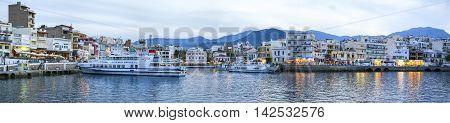 AGIOS NIKOLAOS, GREECE - MAY 2008: Sunset on Old Town of Agios Nikolaos, panoramic landscape with cruise ships, Crete island, Greece, May 2008