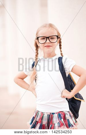 Smiling pupil girl prepare for school wearing glasses and backpack outdoors. Looking at camera. Back to school.