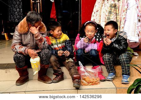Pengzhou China - January 31 2014: Grandmother sitting on a step in front of a clothing store eating snacks with her grandson and two friends