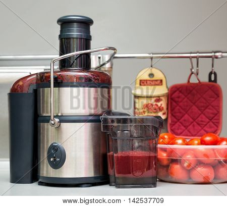 Squeezing tomato juice at home. Juicer in the kitchen.