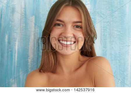 Portrait of the young and beautiful girl with naked shoulders, loose hair and toothy smile