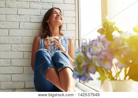 Toothy smile happy girl enjoying a peaceful sunny summer day on the window-sill while relaxing and drinking a cup of coffee. Wearing casual denim jeans and loose light-blue blouse