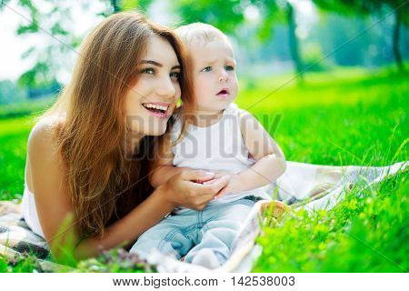 happy young woman and her baby in the park in summertime