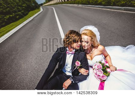 Wedding couple sitting on ground. love symbols on pavement. hearts. people in love. happy bride and groom portraits. man and woman sitting back to back outside on road. newlyweds. wedding day