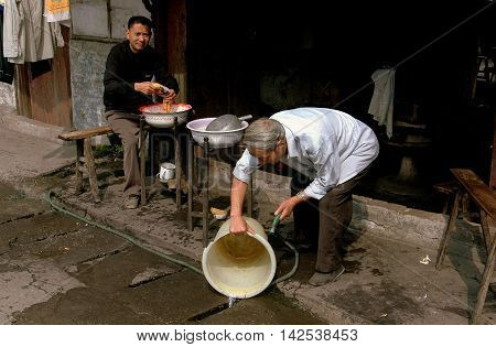 Pengzhou China - September 13, 2006: Barber uses a hose to wash a plastic pail in front of his shop on Hua Lu (Old Street)