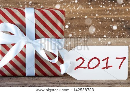 Christmas Gift Or Present On Wooden Background With Snowflakes. Card For Seasons Greetings. White Ribbon With Bow. English Text 2017 For Happy New Year