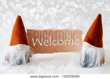 Christmas Greeting Card With Two Bronze Gnomes. Sparkling Bokeh Background With Snow. English Text Welcome