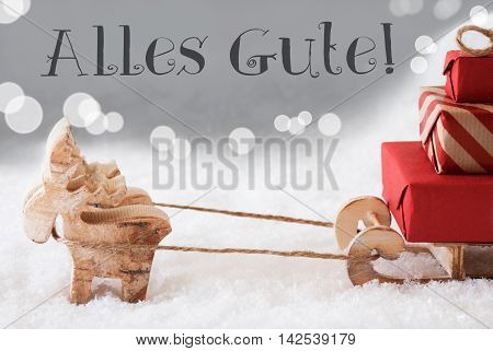 Moose Is Drawing A Sled With Red Gifts Or Presents In Snow. Christmas Card For Seasons Greetings. Silver Background With Bokeh Effect. German Text Alles Gute Means Best Wishes