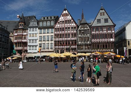 FRANKFURT AM MAIN, GERMANY - JUNE 14, 2015: Tourists in front of the reconstructed half-timbered houses of the Ostzeile at the Romerberg in Frankfurt am Main, Germany.