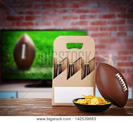 Six pack of beer, snack and ball on wooden table in front of television show of football. Watching football match at home.