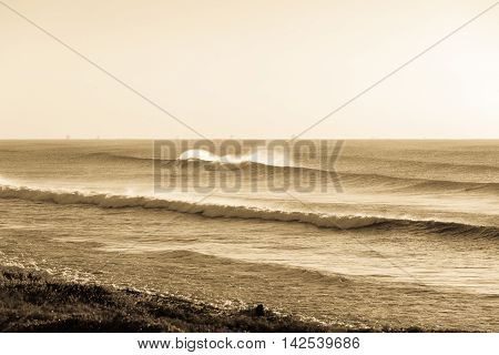 Morning ocean waves crashing along coastline vintage antique sepia tone..