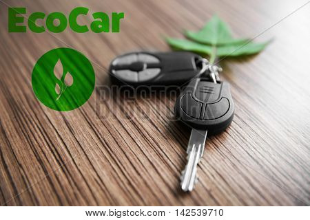 Car key with green leaf trinket and text ecocar on wooden background. Eco transport concept.