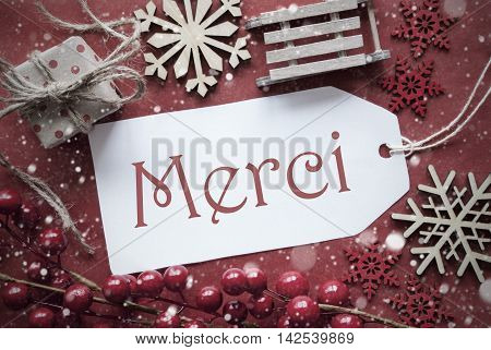 Nostalgic Christmas Decoration Like Gift Or Present, Sleigh. Card For Seasons Greetings With Red Paper Background. French Text Merci Means Thank You