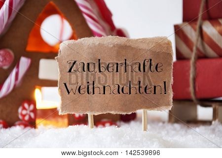 Gingerbread House In Snowy Scenery As Christmas Decoration. Sleigh With Christmas Gifts Or Presents. Label With German Text Zauberhafte Weihnachten Means Magic Christmas