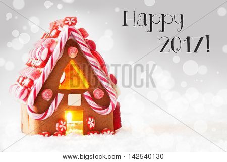 Gingerbread House In Snowy Scenery As Christmas Decoration. Candlelight For Romantic Atmosphere. Silver Background With Bokeh Effect. English Text Happy 2017 For Happy New Year