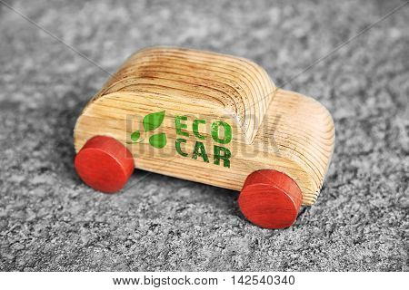 Wooden toy car with text eco car on gray background. Transport and ecology concept.