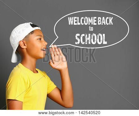 Cute afro american teenager with speech bubble and text welcom back to school on gray background. School concept.