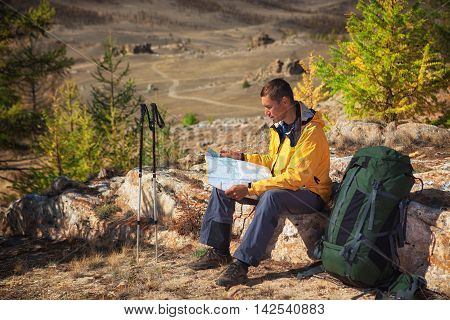 Man tourist backpacker researching map on forest trip while resting. Man hiker searching looking for direction guide. Backpacking summer vacation adventure..
