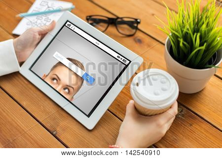 business, education, technology, people and advertisement concept - close up of woman with internet browser search bar on tablet pc computer screen and coffee cup on wooden table
