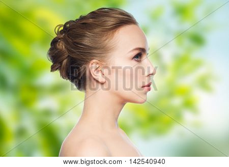 health, people, eco and beauty concept - beautiful young woman face over green natural background