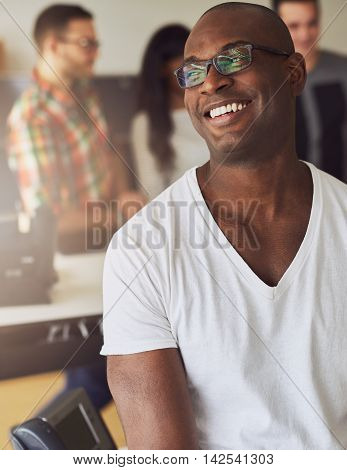 Handsome smiling worker in white shirt and eyeglasses with three co-workers behind him in meeting
