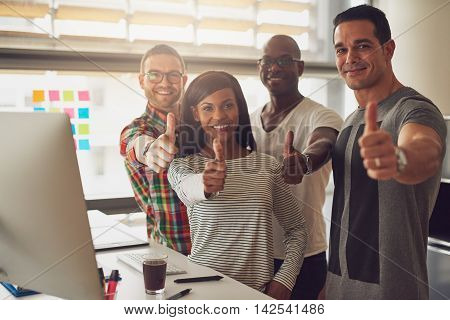 Diverse group of four business partners or entrepreneurs holding their thumbs up in approval or to like something in their office