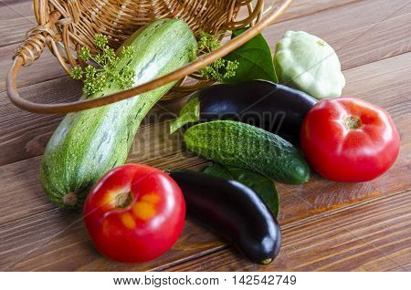 Vegetable picture with natural tomato cucumber eggplant fennel and basket on a wooden background