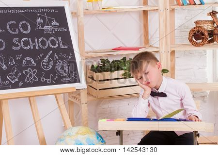 Boy during a lesson at school tired of playing. The concept of a frustrated student