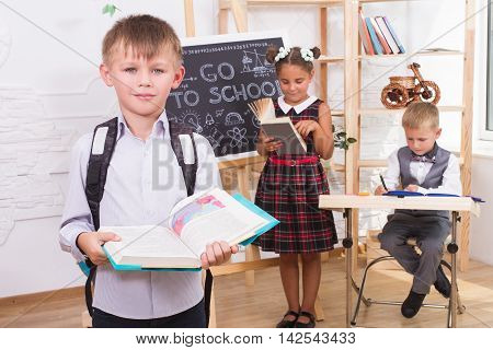 Portrait of a boy reading a book on the background of their classmates. On the back of his backpack . The concept of education and children's knowledge