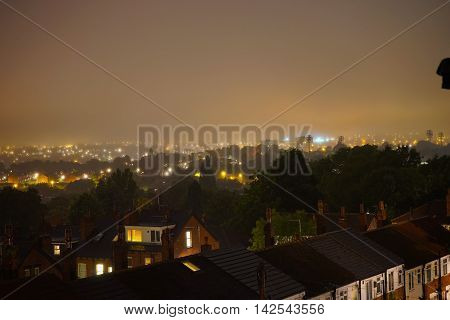 A hazy night in Leeds overlooking a beautifully lit residential area