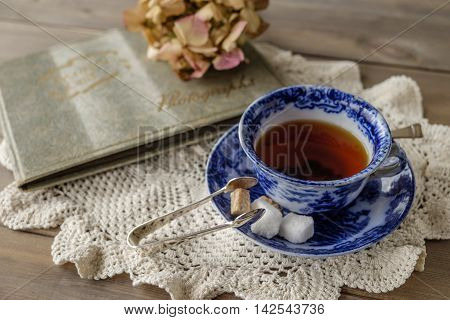 Antique blue and white china cup and saucer with tea and sugar cubes on lace cloth on wooden table with out of focus faded flower and old photograph album in background