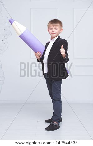Boy in school uniform stands in the background of the large pencils and shows class. concept of education and children's knowledge