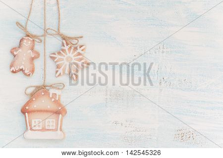 Christmas cookies as a gingerbread man house and snowflake on a light wooden background
