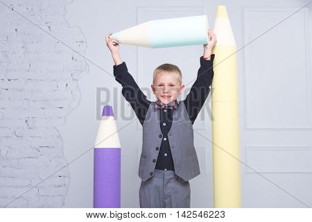 Cute boy standing with a huge pencil. Education and children's knowledge
