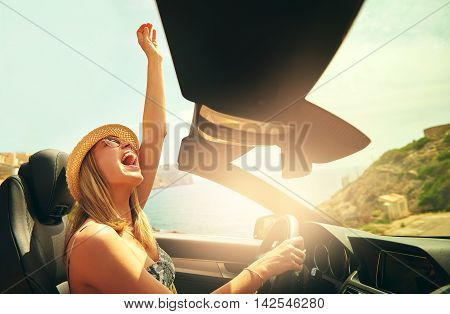 Excited pretty woman with hat and sunglasses reaching her fist in air as if to celebrate in convertible top automobile