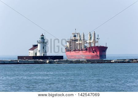 A foreign ship passes the lighthouse style navigation beacon at the entrance to the Port of Cleveland on Lake Erie