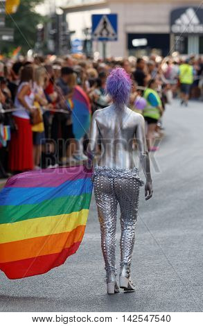 STOCKHOLM SWEDEN - JUL 30 2016: Half naked woman covered with silver body paint carrying the rainbow pride flag in the Pride parade July 30 2016 in Stockholm Sweden